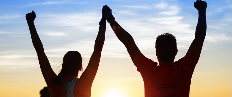 Image of two people raising their hands to the sky during a sunset